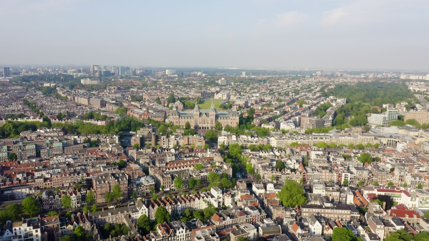 Amsterdam, Netherlands. Museum ( Rijksmuseum ). The building of the XIX century. Flying over the rooftops of the city, Aerial View, Departure of the camera | Shutterstock HD Video #1046734024