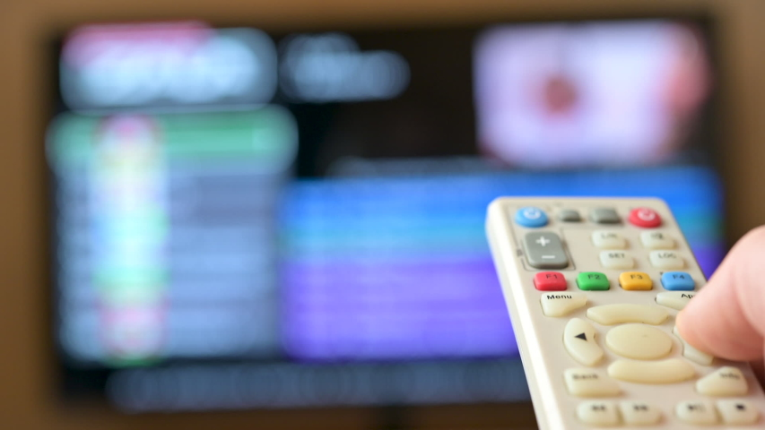Watch TV. Closeup male hand switches television channels, on the background of the television screen. Interactive tv | Shutterstock HD Video #1046822194