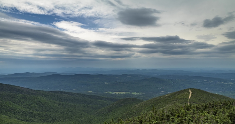 Time lapse from the top of Canon Mountain mid day in New Hampshire USA. Clouds flying overhead with view of some farms far below. Includes 2 versions, one tilting down and 1 stationary.   Shutterstock HD Video #1046823064