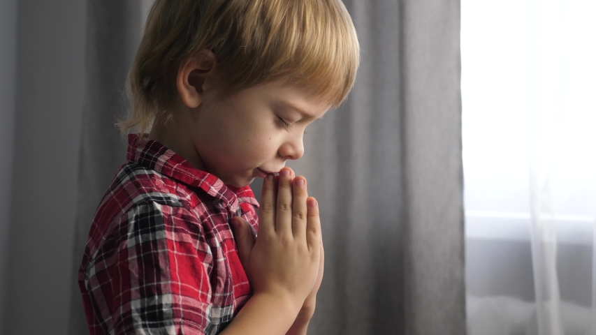 Little son boy prays lifestyle bedtime religion concept. prayer child indoors praying by bed in front of window | Shutterstock HD Video #1046890894