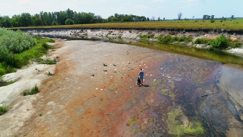 Aerial view of man who collects plastic trash on the banks of a dry and polluted river, lake. Camera is moving away. Environmental pollution problem concept. Ecological catastrophy. 4K drone footage | Shutterstock HD Video #1046928274