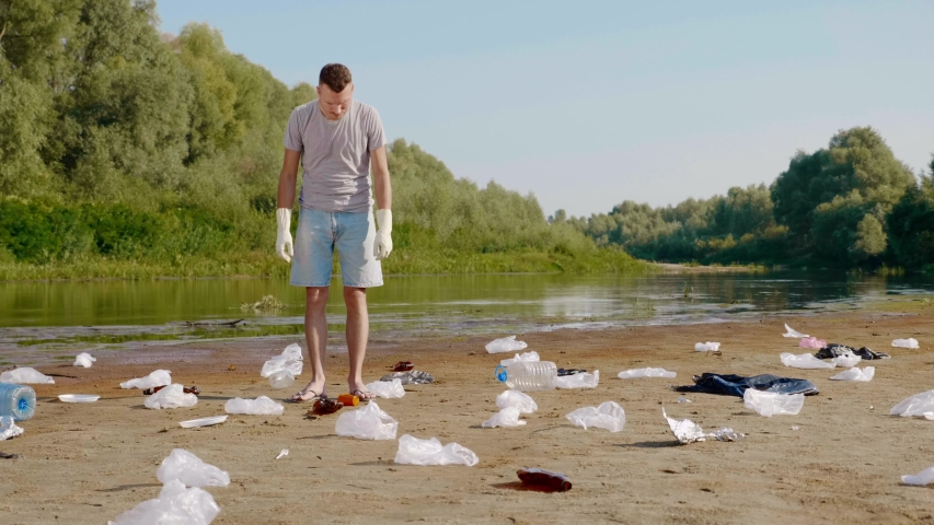 Man in a gray t-shirt and blue denim shorts is picks up plastic trash on the banks of a dry and polluted river or lake and shows dislike. Ecological catastrophy. Anthropogenic influence. 4K footage. | Shutterstock HD Video #1046929114