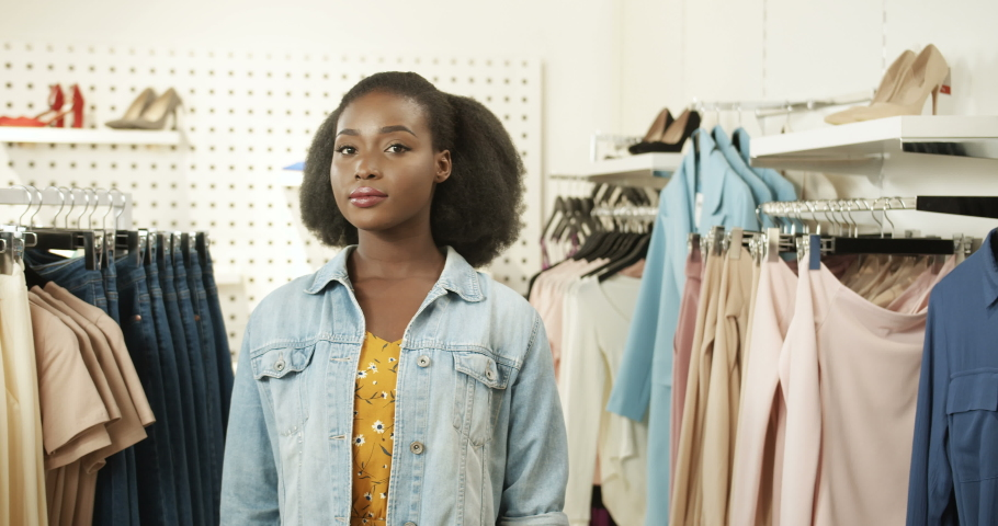 Portrait of happy young African American charming woman smiling joyfully to camera in clothing store. Pretty girl laughing at shopping in shop of fancy clothes. Female fashion buyer. | Shutterstock HD Video #1046966164