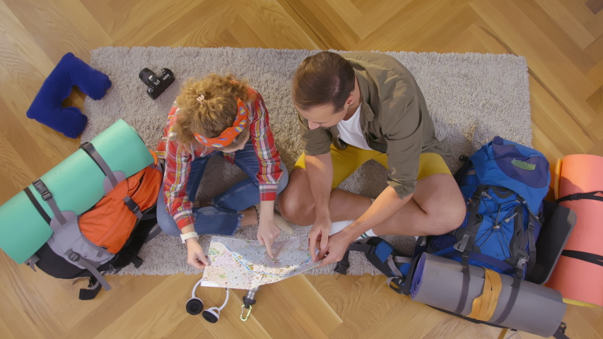 Top view of couple planning next hiking tour destination using map. Young people ready for vacation studying map sitting on floor among hiking equipment - Relationship and Traveling lifestyle concept | Shutterstock HD Video #1046968894