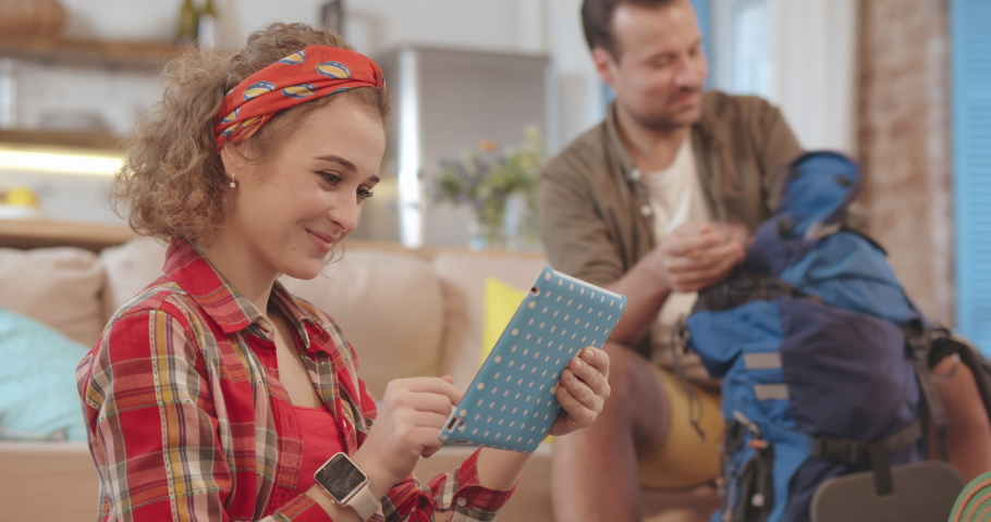 Young girl learn route in new city using digital tablet, her husband packing backpack on background. Happy boyfriend and girlfriend preparing for new adventure. | Shutterstock HD Video #1046968954