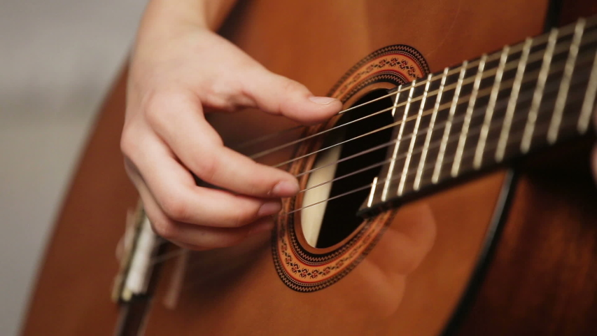 Womans hands playing acoustic guitar  | Shutterstock HD Video #1046969434