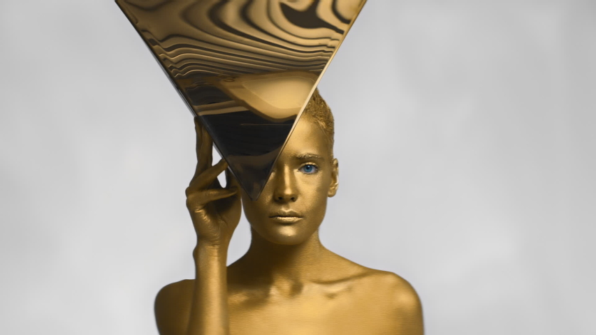 Slender attractive girl with gold coating looks out from metal triangle, slim fashion model in Studio is covered with single color golden paint touches metallic shiny decoration on white background | Shutterstock HD Video #1047018184