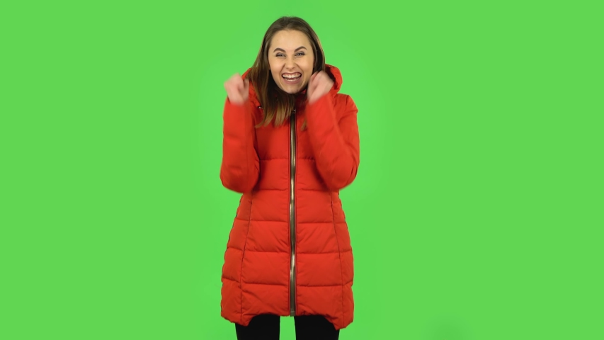 Lovely girl in red down jacket is looking at camera with excitement, then celebrating her victory triumph. Green screen | Shutterstock HD Video #1047105574