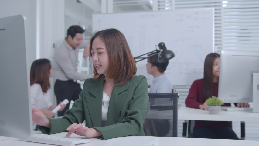 Excited Asian Businesswoman Sitting at her office desk arms raised celebration of successful project, job promotion. Her Colleagues are Clapping and Happy. Successful Businesswoman Concept. | Shutterstock HD Video #1047146524