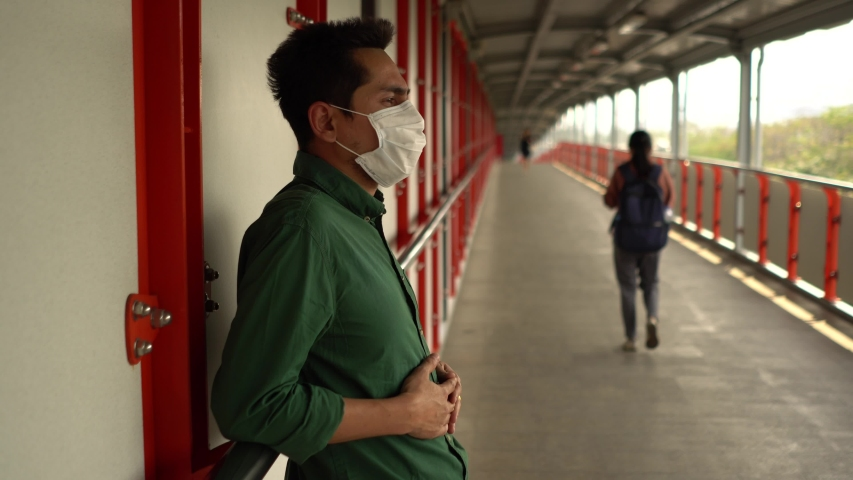 A man wearing mask protective for spreading of disease virus Covid-19 and air smog pollution with PM 2.5 standing on skywalk at chatuchak district in  Bangkok city, Thailand. | Shutterstock HD Video #1047322594