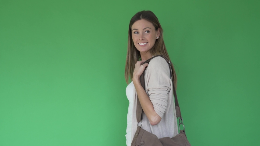 Woman walking with purse and smartphone, green screen | Shutterstock HD Video #1047332734