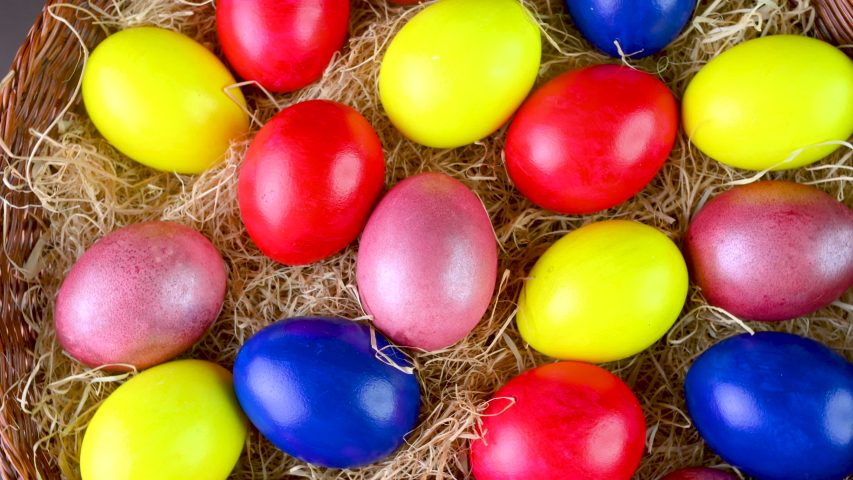 Closeup top view Colorful easter eggs lie on a bacon in a basket. 360 rotation. Easter decorations. Easter concept background. | Shutterstock HD Video #1047520714