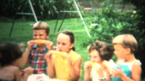 IOWA, USA - JULY 1954: Kids eating freshly picked roasted corn on the cob from the farm while they sit at the outdoor table with family and friends.