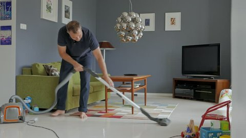 Man cleaning house with vacuum cleaner, toys spread out