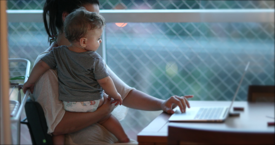 Mother multi-tasking, holding baby infant and using computer laptop at home. Candid authentic and real life mom working and parenting | Shutterstock HD Video #1048055704
