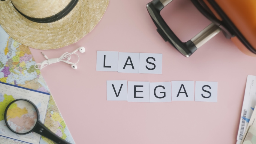 Top view hands laying on pink desk word LAS VEGAS | Shutterstock HD Video #1049271694