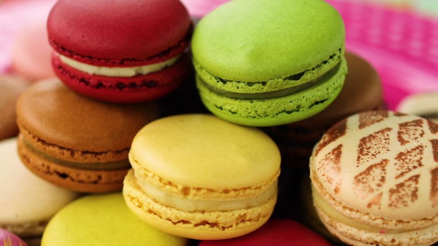 Macarons tower on dessert plate at home. Cute retro vintage pink plate on checkered tablecloth easter table decoration home kitchen. Assortment of pastel colored macaron of different flavors. | Shutterstock HD Video #1049478094