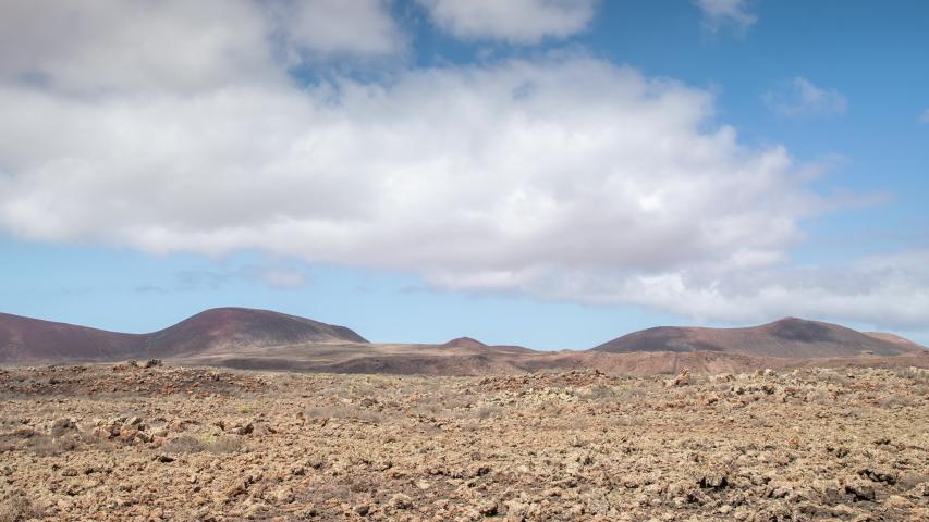 Panning timelapse of clouds passing over wild arid landscape of Volcano de Bayuyo in Fuerteventura. | Shutterstock HD Video #1049664034