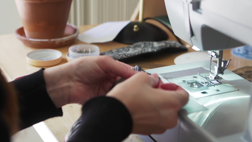 An experienced fashion designer working at home creating, stitching and sewing face masks from recycled fabric as a protection against viruses, disease and germs | Shutterstock HD Video #1049712394