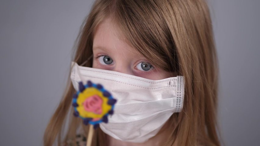 Close-up of a little blonde girl in a protective mask studying a plasticine model of the virus, project activity with distance learning. | Shutterstock HD Video #1049712484