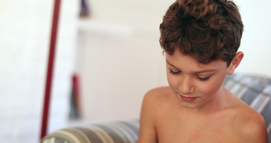 Candid kid using tablet sitted on sofa playing game | Shutterstock HD Video #1049719174