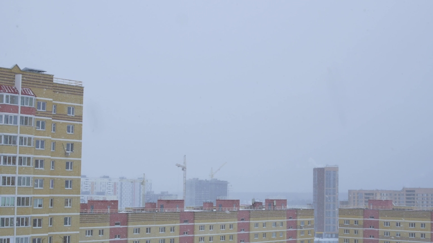 Large flakes of snow falling from the sky in the city overlooking the roofs of multi-story buildings and construction cranes | Shutterstock HD Video #1049864914