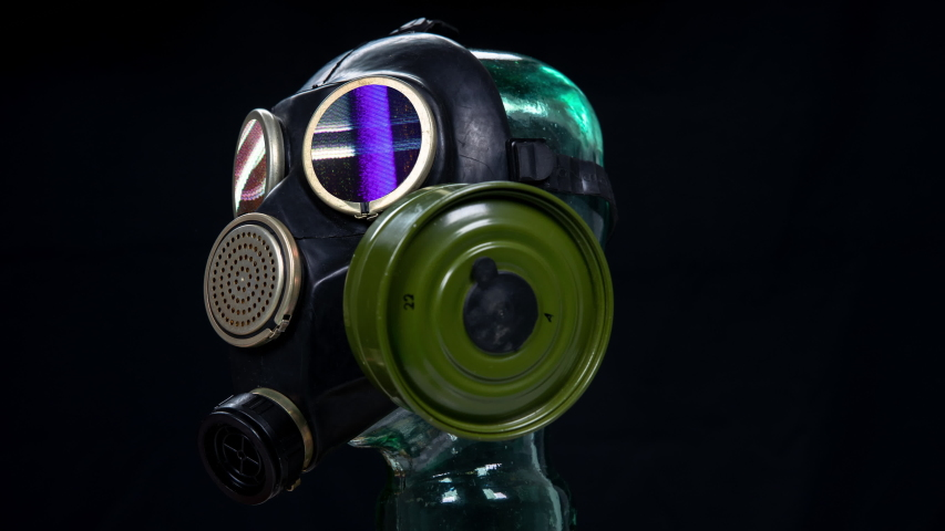 A gas mask for protection from viruses against black background with static in the eye pieces | Shutterstock HD Video #1049958364