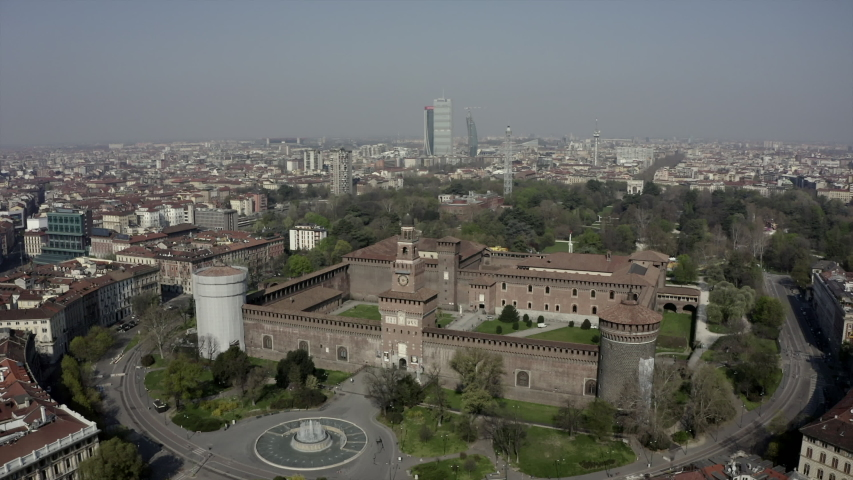 Everyday life in Milan, Italy during COVID-19 epidemic. Milano, Italian city and coronavirus quarantine. Aerial view of historic building: Castello Sforzesco seen from drone flying in sky | Shutterstock HD Video #1050081664