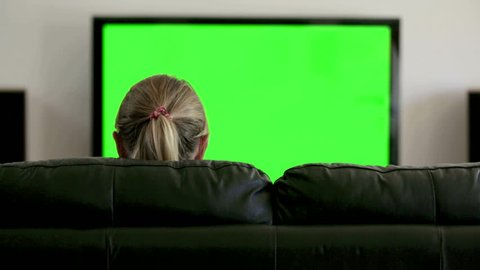 Back view of woman sitting on black leather couch watching TV; she clasps her hands behind her head. Green screen.