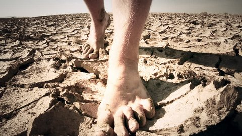 Barefoot man walks through deserted land on cracked dry surface toward camera. Conceptual background slow motion close up video