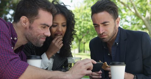 Group of young friends watching video on cell phone while eating at outdoor caf_