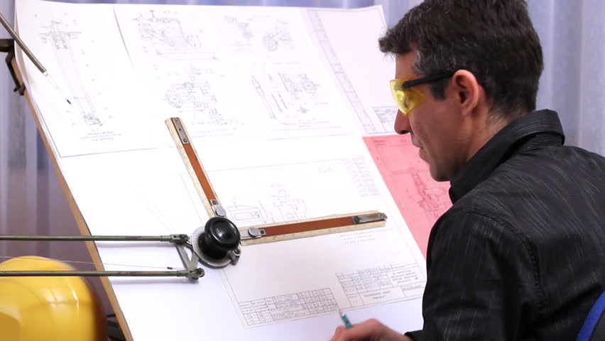 Mechanical engineer analyzes his design.  Man Draws a Technical Drawing on Drawing Board. Man Sitting at Drafting Board. Architect Making Plans at Drawing Board in an office.