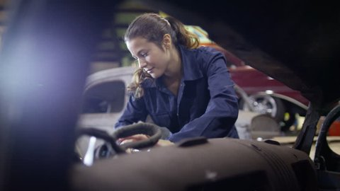 4K Attractive female mechanic working on car engine in garage workshop