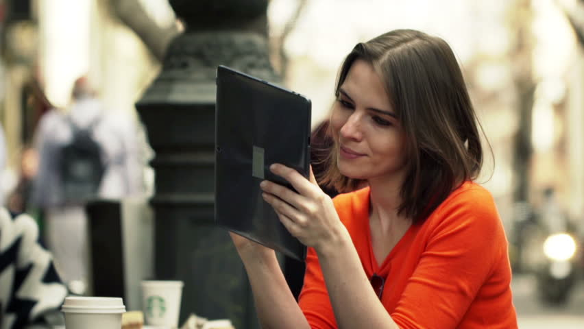 Young woman using tablet computer while sitting in cafe in city