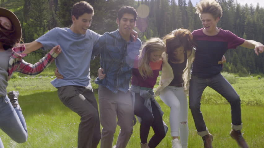 Group Of Playful Teens Stand Arm In Arm, Then They Jump In The Air, And All Fall Down. Laughing (Slow Motion)