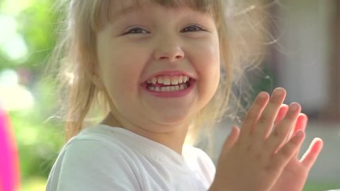 Little Girl Clapping hands and laughing outdoors. Cute three years old child enjoying nature outdoors. Healthy carefree kid playing outside in summer park. Full HD 1080p High speed camera, slow motion