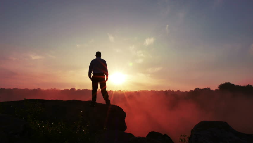 Silhouette of meditating man (prayer) at sunrise time. 4K 3840x2160