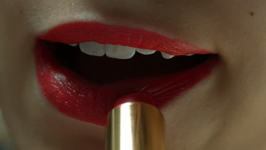 A young woman putting on red lipstick inside | Shutterstock HD Video #10663163