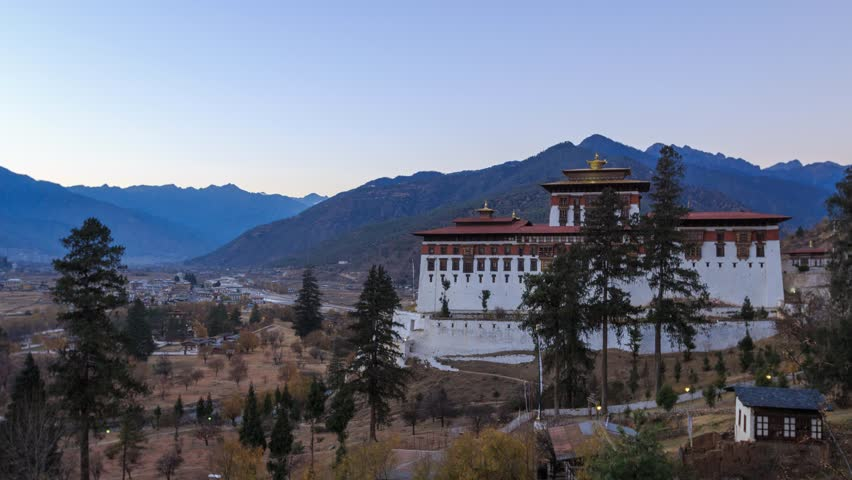 Timelapse of The Paro Rinpung Dzong and The Ta Dzong (Bhutan National Museum) from day to night in late autumn with city of Paro as background, Paro, Bhutan.