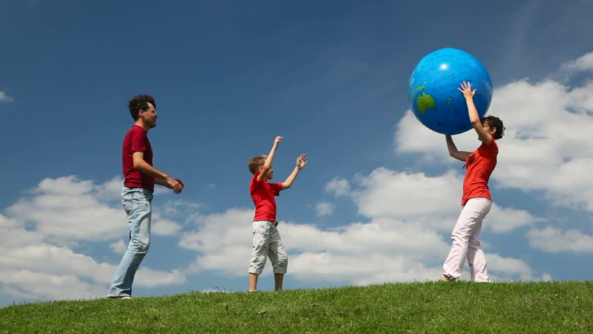 parents and son playing with big inflatable ball in a meadow