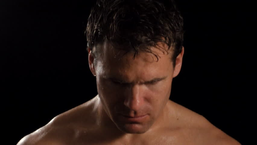 Intense sweaty male athlete looks into camera.