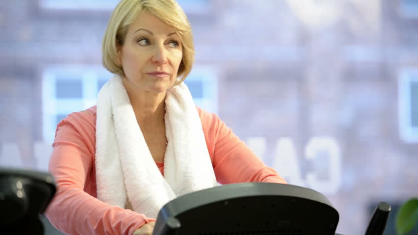 Mature woman exercising at health club; HD Photo JPEG