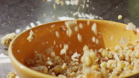 CLOSE UP: Whole grain cereal falling into bowl for breakfast