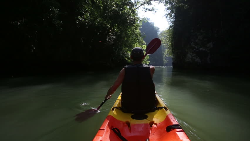 Old man in life-vest back-side view drifts on kayak down river along sunlit canyon | Shutterstock HD Video #10726214