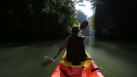 old man in life-vest back-side view drifts on kayak down river along sunlit canyon