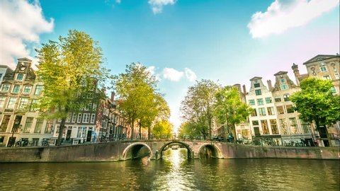 AMSTERDAM, NETHERLANDS - JULY 07 : Boats on the Amsterdam  canals. Time Lapse. 4K ULTRA HD video. July 07, 2015.  A nice summer day on Amsterdam canals with old houses and bridge.