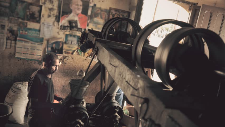 Man grinding corn with obsolete machinery, San Salvador. 4k