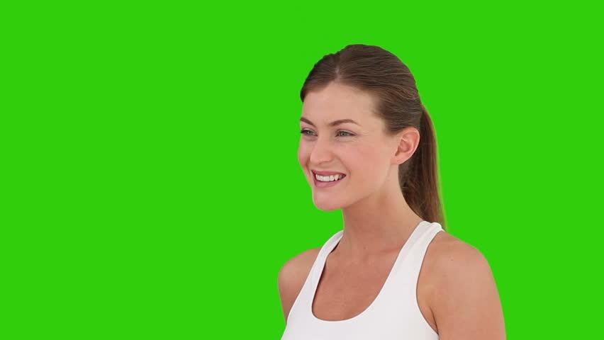 Cute brunette woman drinking orange juice against a green screen