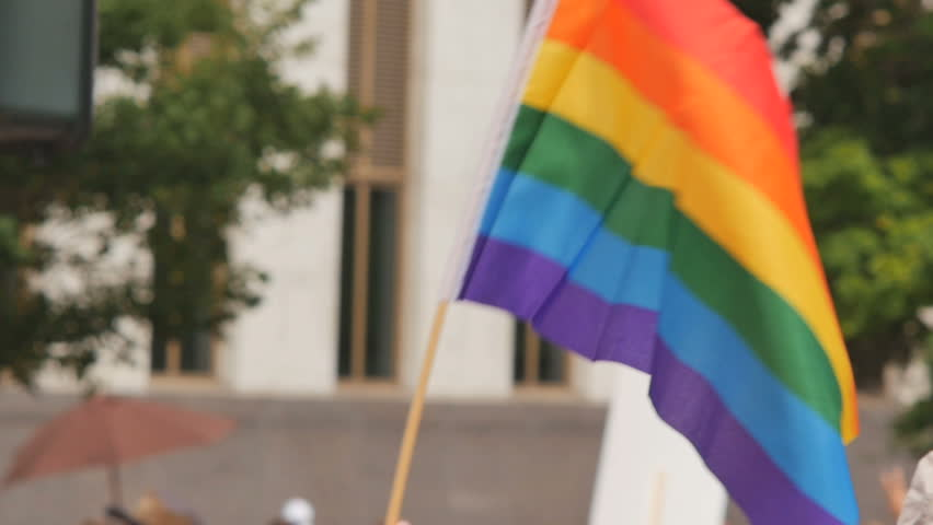 A rainbow flag waves as people walk by in the background with other rainbow flags and protest signs. slow motion. Symbol of LGBT GLBT transgender rights love equality