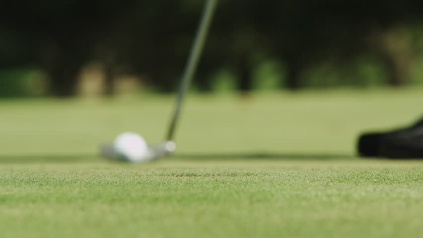 Close up of a guy making a put at the golf course.